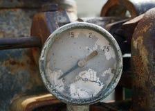 Vieille mesure cassée avec des traces des nombres sur le cadran sur un grand vieux moteur rouillé photos libres de droits