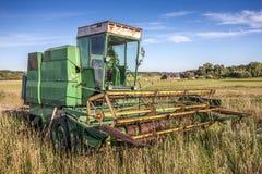 Vieille moissonneuse verte sur un champ Image libre de droits