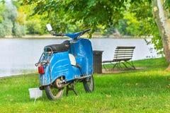 Vieille moto bleue à l'au bord du lac avec les arbres et le banc Image libre de droits