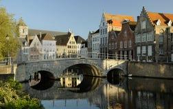 Vieille passerelle en pierre au-dessus d'un fleuve à Bruges Images stock