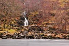 Vieille passerelle romaine avec une cascade grande cascadant derri?re image libre de droits