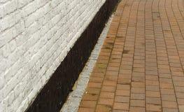 Vieille petite rue avec le trottoir et le mur blanc Photos stock