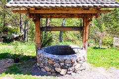 Vieille pierre bien d'un jardin rustique Photographie stock