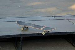Vieille planche à roulettes utilisée au parc de patin image stock