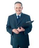 Vieille planchette de sourire de fixation d'homme d'affaires Photographie stock libre de droits