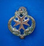 Vieille poignée de dauphin de porte avec la croix maltaise sur la porte azurée, La Valette, Malte images libres de droits