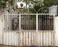 Vieille porte blanche menant à un jardin de village Images libres de droits