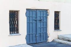 Vieille porte bleue en acier avec des fenêtres sur le trellis dessus Photo libre de droits