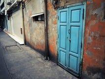 Vieille porte bleue sur un mur rouge photographie stock