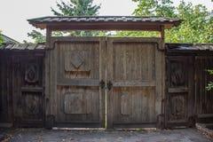 Vieille porte en bois avec des ornements et un petit toit avec des guichets des deux côtés de eux Photos stock