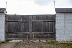 Vieille porte en bois avec le chemin de terre et deux obstacles en bois dans une barrière grise de brique photo libre de droits