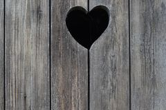 Vieille porte en bois minable avec le coeur dans les toilettes rurales Photos libres de droits