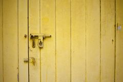 Vieille porte jaune de couleur avec un verrou ouvert Photographie stock