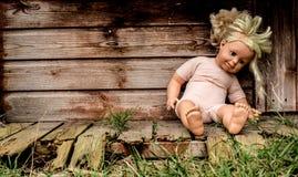 Vieille poupée négligée devant un hangar abandonné Image libre de droits