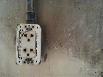 vieille prise électrique cassée sur le mur sale de ciment Photo libre de droits
