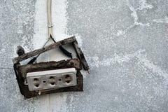 vieille prise électrique cassée sur le mur sale de ciment Images stock