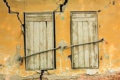 Vieille rétro fenêtre grunge de paires avec les volets en bois au mur criqué jaune Photo libre de droits