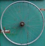 Vieille roue de bicyclette sur le fond sale en bois vert Photo libre de droits