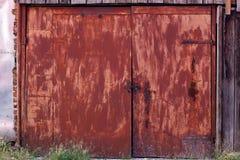 Vieille, rouillée porte à deux battants rouge, solidement fermée Image stock