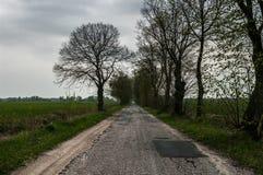 Vieille route de saleté, disparaissant dans le champ Photo stock