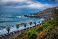 Vieille route le long de l'océan, des vagues, des palmiers et des montagnes Image stock