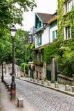 Vieille rue avec du charme de colline de Montmartre Paris, France Photographie stock