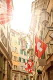 Vieille rue avec les drapeaux suisses, rayons de soleil Photo stock