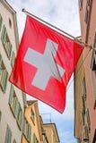 Vieille rue avec les drapeaux suisses, rayons de soleil Photos stock