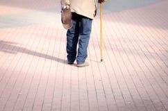 Vieille seule promenade déprimée d'homme en bas de la rue avec la vue isolée et perdue de sentiment de bâton ou de canne de march images stock