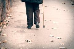 Vieille seule promenade déprimée de femme en bas de la rue avec la vue isolée et perdue de sentiment de bâton ou de canne de marc photographie stock