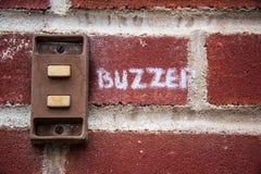 Vieille sonnerie rouillée en métal sur un mur de briques Photos stock