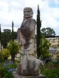 Vieille statue orientale avec de jeunes cerfs communs Images libres de droits