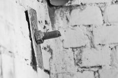 Vieille tête de vis dans la brique Image noire et blanche avec du vieux Sc rouillé Images libres de droits