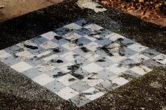 Vieille table en pierre négligée avec un damier Image stock