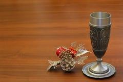 Vieille tasse antique de vin de fonte de bidon sur le support de bidon et bouquet décoratif de nouvelle année sur le fond en bois photo stock