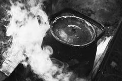Vieille théière noire utilisée avec l'eau bouillante images stock
