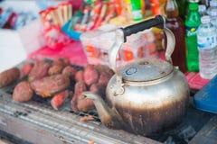 Vieille théière sur la patate douce de fourneau et de gril Photo stock