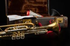 Vieille trompette couverte de patine dans un cas Un instrument de musique historique de vent et une valise photos stock