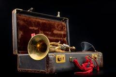 Vieille trompette couverte de patine dans un cas Un instrument de musique historique de vent et une valise photographie stock libre de droits