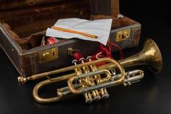 Vieille trompette couverte de patine dans un cas Un instrument de musique historique de vent et une valise photo stock