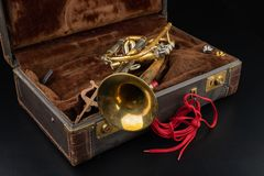 Vieille trompette couverte de patine dans un cas Un instrument de musique historique de vent et une valise photos libres de droits