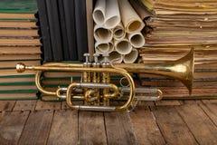 Vieille trompette couverte de patine sur une vieille table en bois Instrument de musique et vieux livres images libres de droits