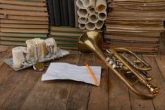 Vieille trompette couverte de patine sur une vieille table en bois Instrument de musique et vieux livres image libre de droits