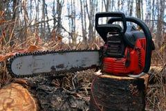Vieille tronçonneuse rouge et bois de chauffage coupé Photo libre de droits