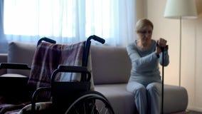 Vieille veuve bouleversée s'asseyant sur le sofa, mari absent, fauteuil roulant vide dans la chambre photo stock