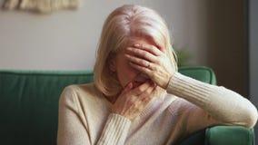 Vieille veuve s'affligeante triste désespérée pleurant couvrant le visage de mains banque de vidéos