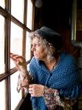 Vieille vieille femme à la fenêtre Images libres de droits