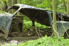 Vieille voiture abandonnée dans la forêt image stock