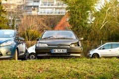 Vieille voiture de Peugeot avec le phare cassé garé photos stock