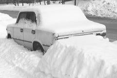 Vieille voiture en hiver dans la neige sur la route, photo noire et blanche Photos libres de droits